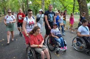 asystent pomaga osobie na wózku, razem idą z grupą osób w parku